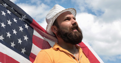 man, beard, fedora, blue sky, america, american flag, wind, billow, heroic, bold, intrusive, pirate, this land is your land, steal, vote, politician, president, politics, dumb, ignorant